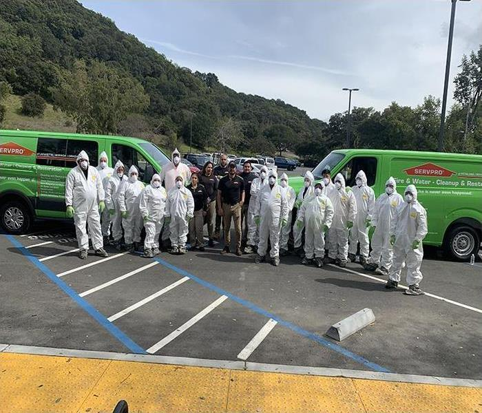 A group photo of SERVPRO professionals in a parking lot with two vans parked on the left and right.