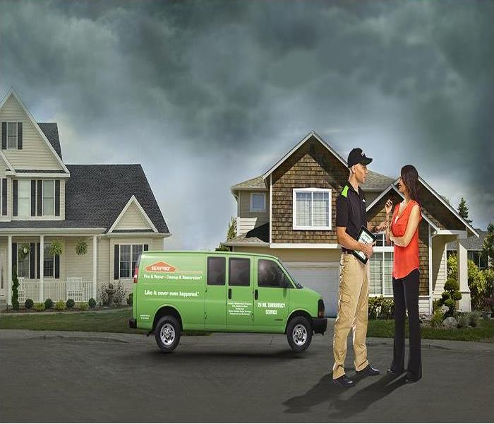 A SERVPRO van in the middle of a neighborhood between two homes. With an agent and woman on the right, under a stormy sky.